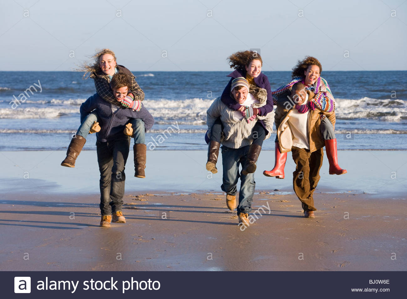 Friends giving piggyback rides at beach - Stock Image
