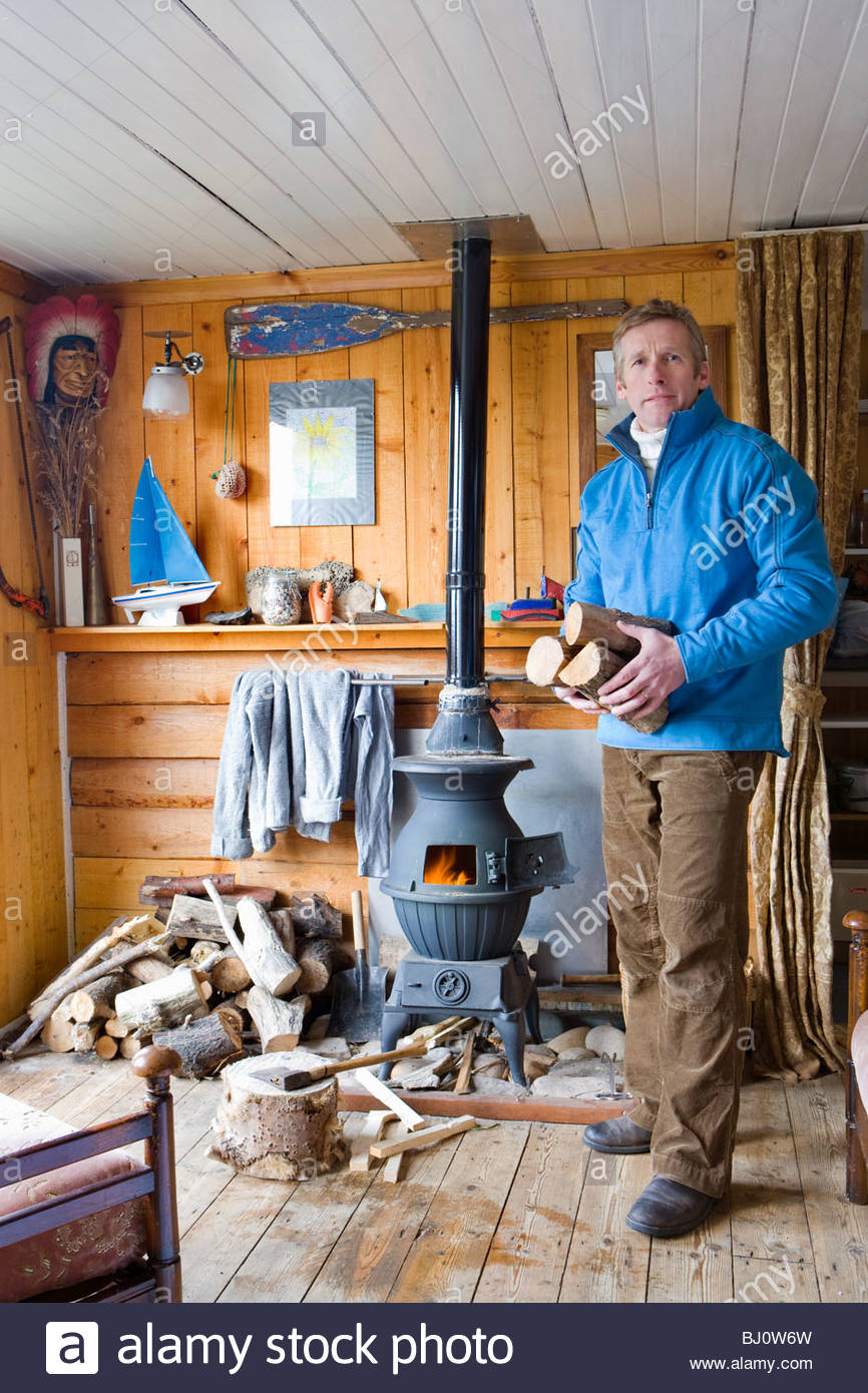 Man in living room putting log into wood burning stove - Stock Image