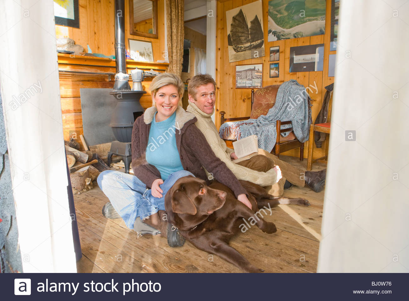 Couple relaxing in living room with pet dog - Stock Image