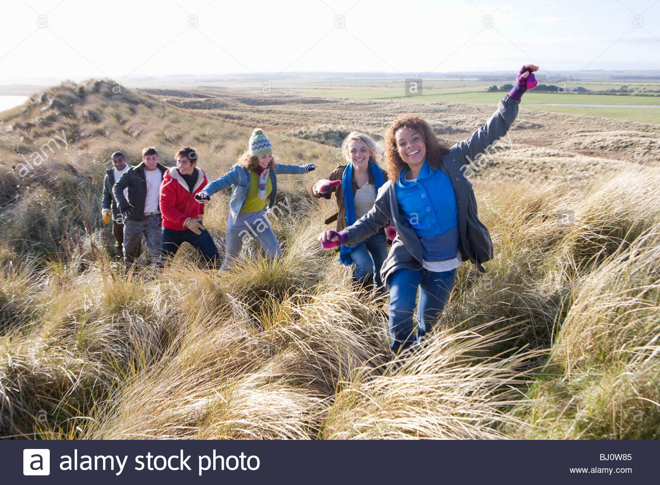 Friends walking on sand dune - Stock Image