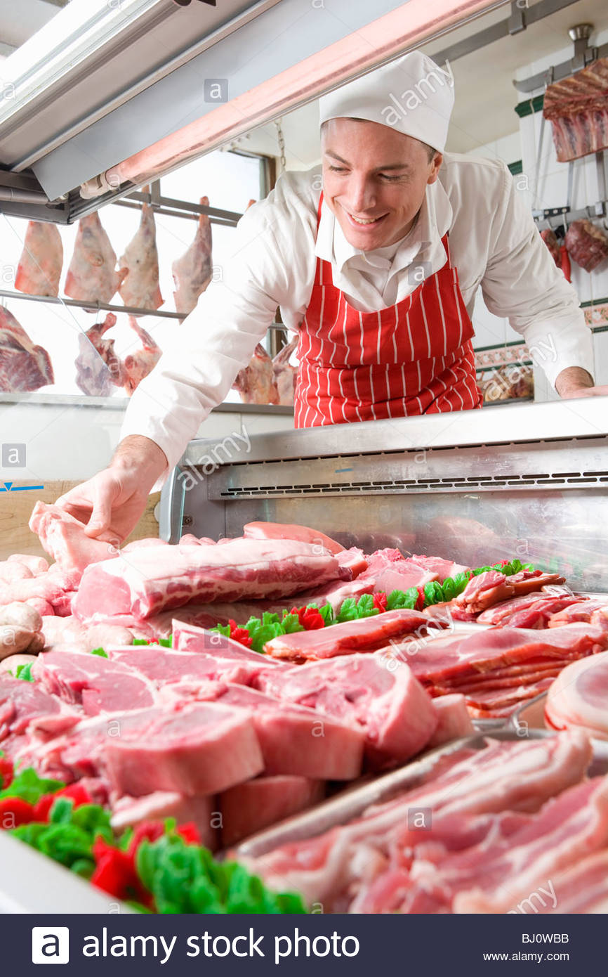 Smiling butcher arranging meat in display case - Stock Image