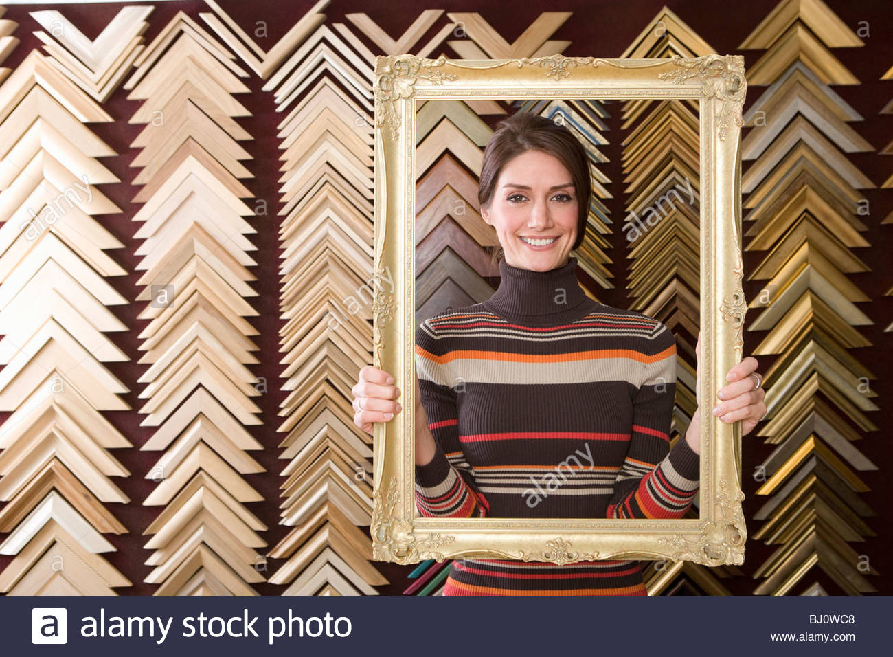 Clerk lifting gold frame in frame shop - Stock Image