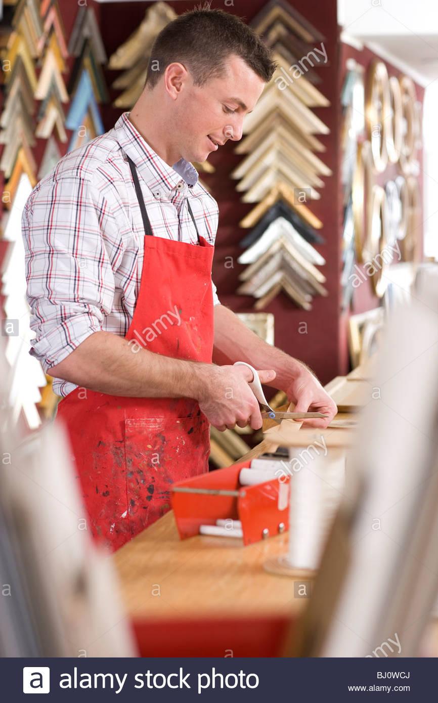 Craftsman working on frame in frame shop - Stock Image