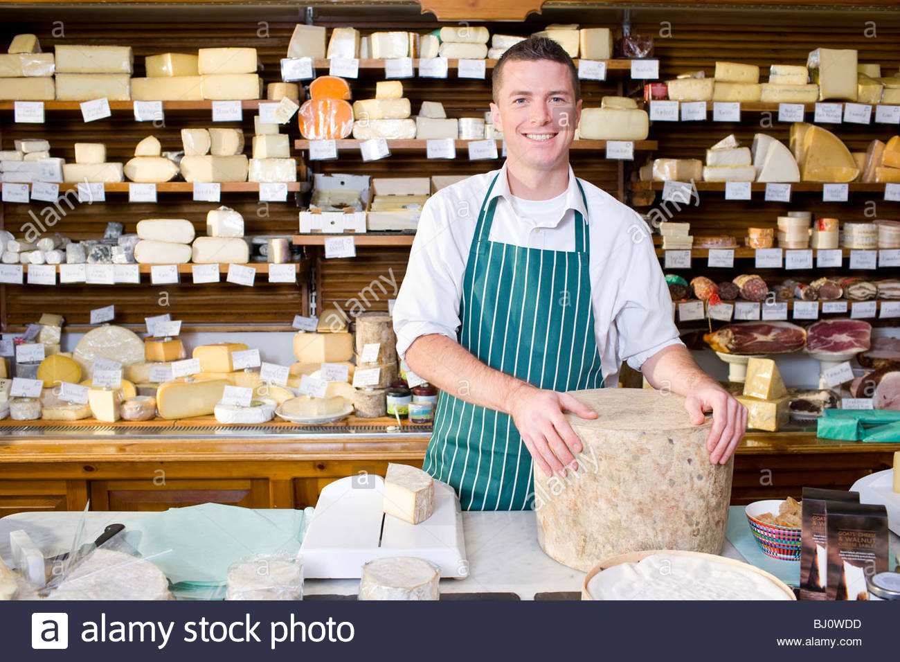 Salesman standing at counter with cheese in cheese shop - Stock Image