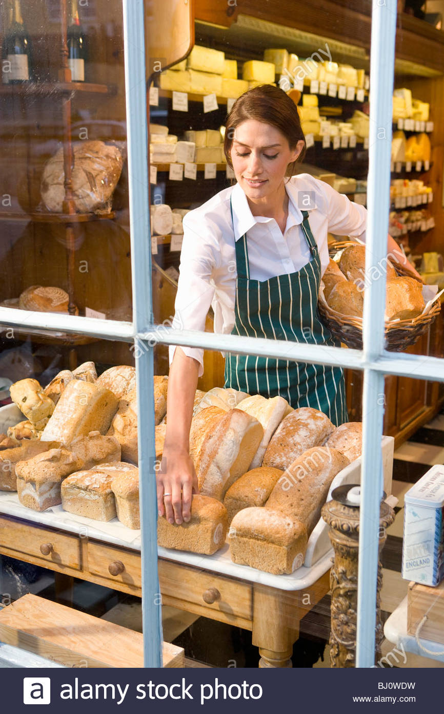 Saleswoman arranging fresh loaves of bread in cheese shop window - Stock Image