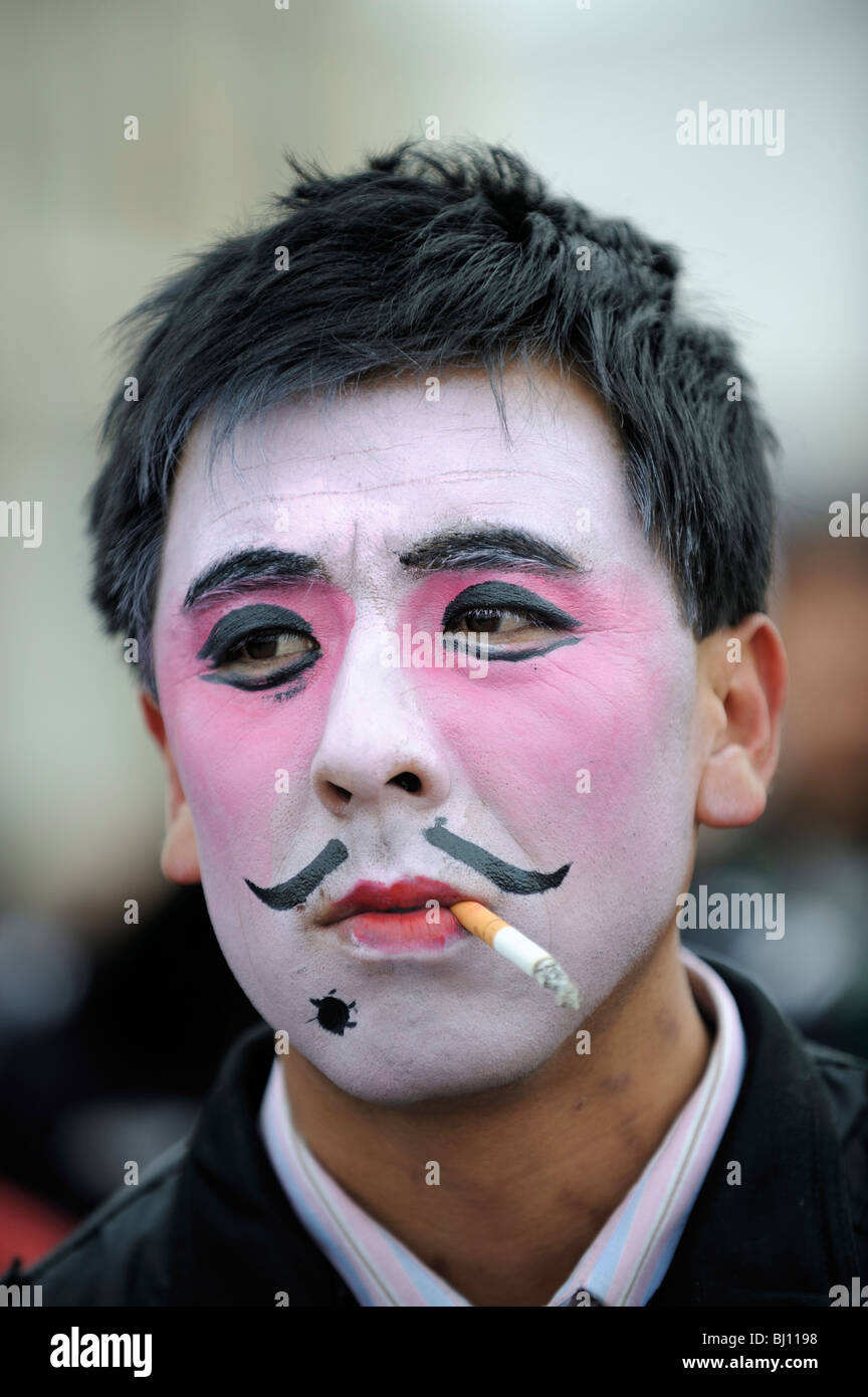 Chinese man with theatrical makeup smoking while Spring Festival performing in Yuxian, Hebei, China. 28-Feb-2010