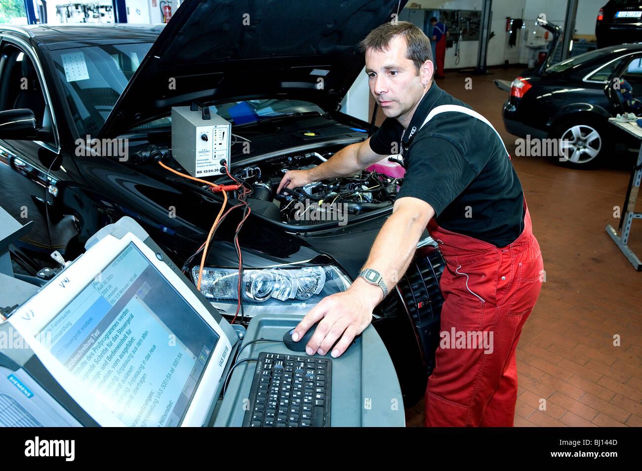 Mechanic checking the fault recorder of a car in search for errors - Stock Image