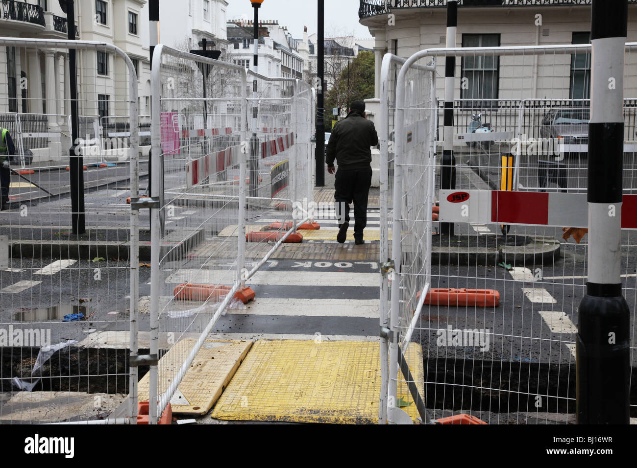 Man crossing the road with construction works - Stock Image