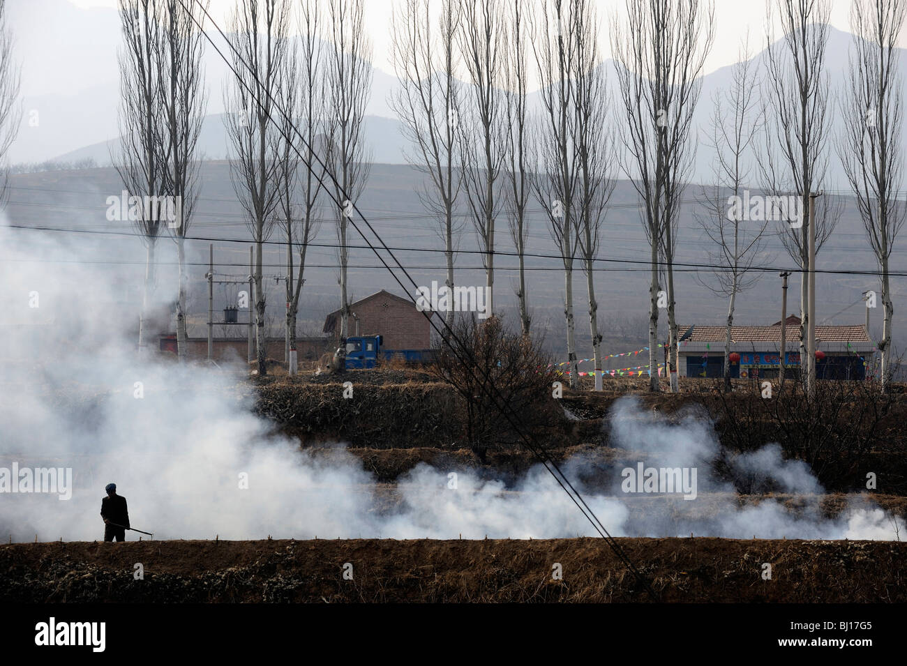 Farmers burning straw in a village in Zhuozhou, Hebei province, China. 27-Feb-2010 - Stock Image