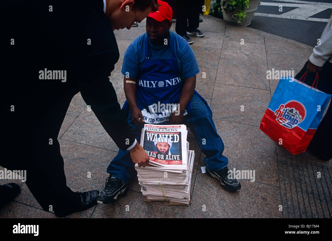 New Yorker bends down to buy latest copy of the New York Daily News with Osama Bin Laden 'Wanted Dead or Alive' - Stock Image