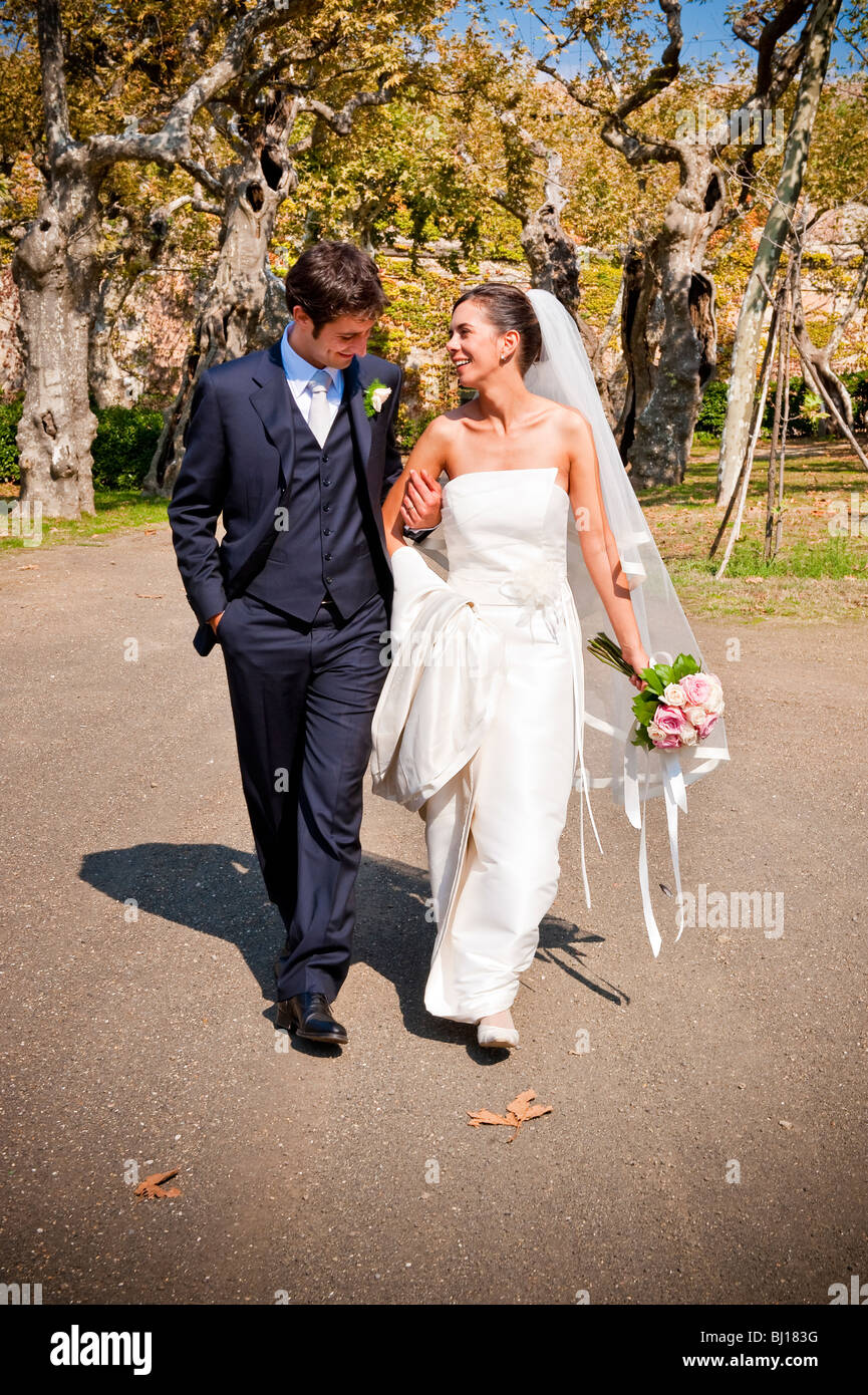 Bride and groom walking in a park - Stock Image