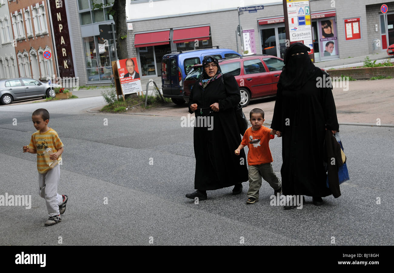 Two women wearing  a black  yashmak or  yashmac or yasmak  crossing a street in Hamburg, Germany with two children - Stock Image