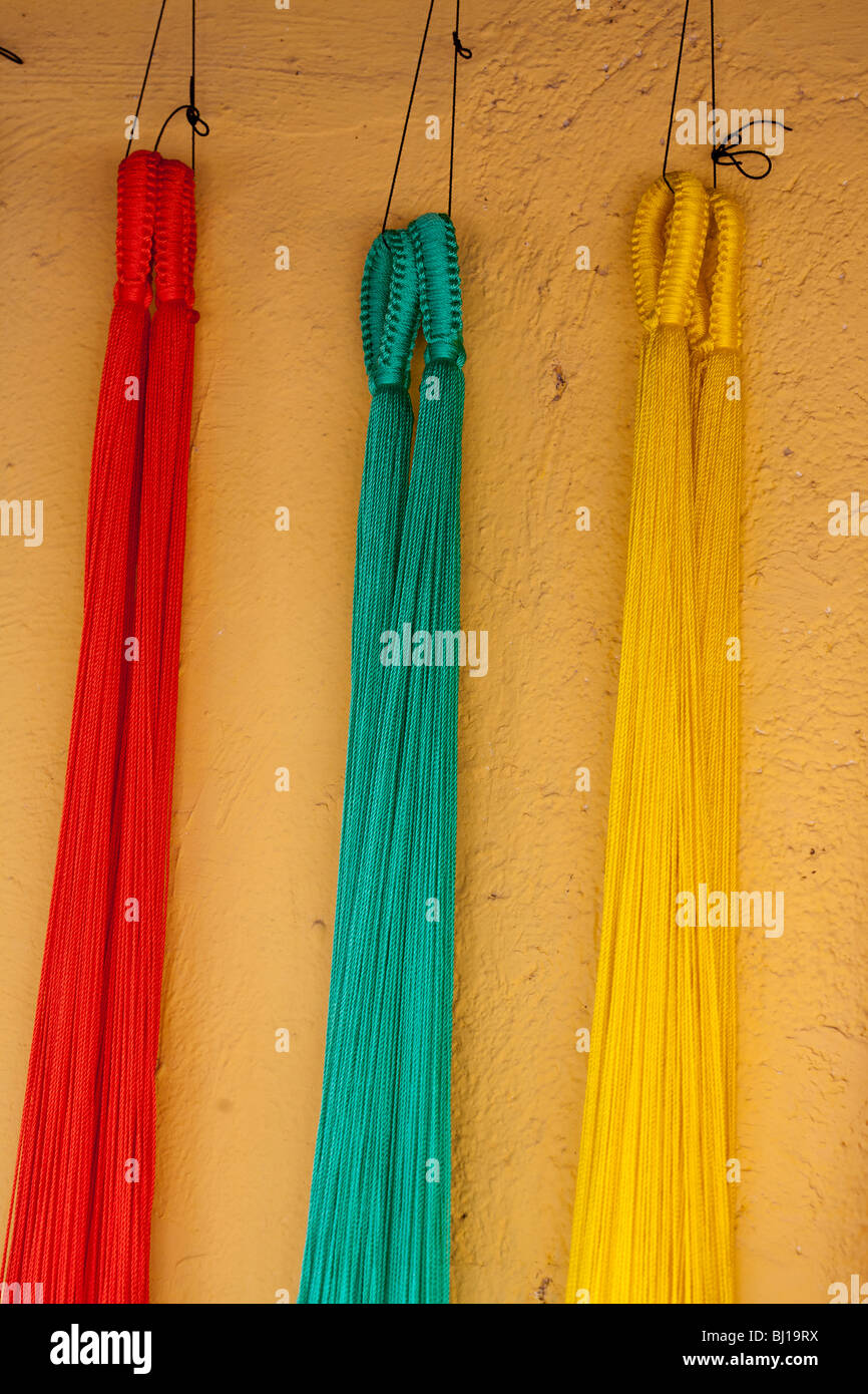 Hanging brightly coloured Hammocks. Three hammocks red, aqua and yellow hang on a yellow wall. Tulum, Quintana Roo, - Stock Image