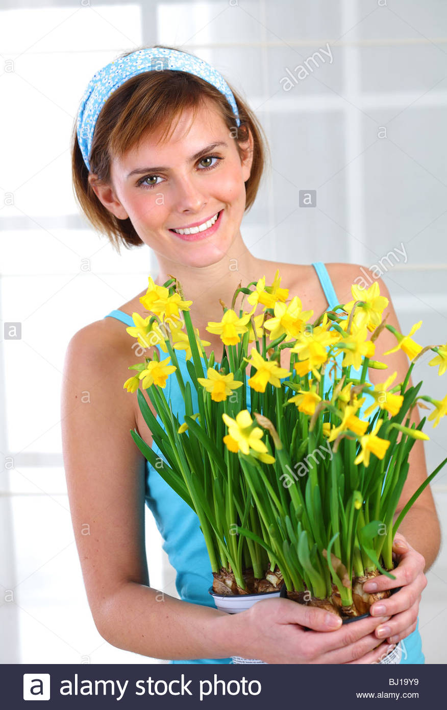young woman holding bunch of daffodils Stock Photo