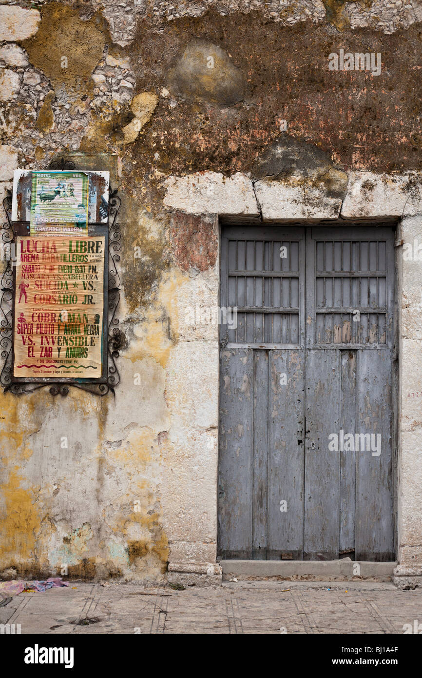 Wrestling and Bull Fighting: Lucha Libre. Two posters compete for attention on a well weathered Merida wall. - Stock Image