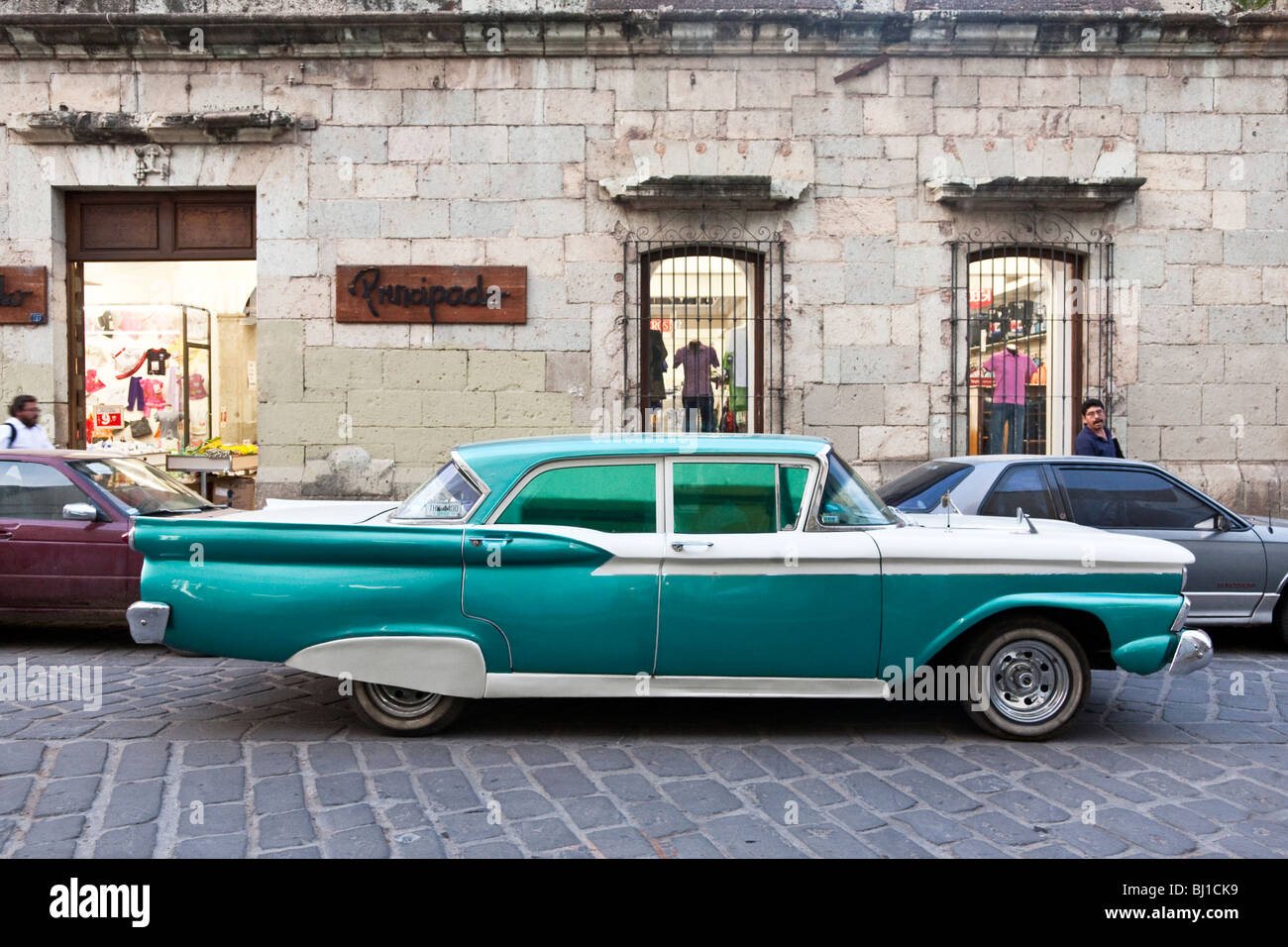 two tone aqua & white fifties Ford restored to finny glory sits on Oaxaca City street in front of boutique Oaxaca - Stock Image