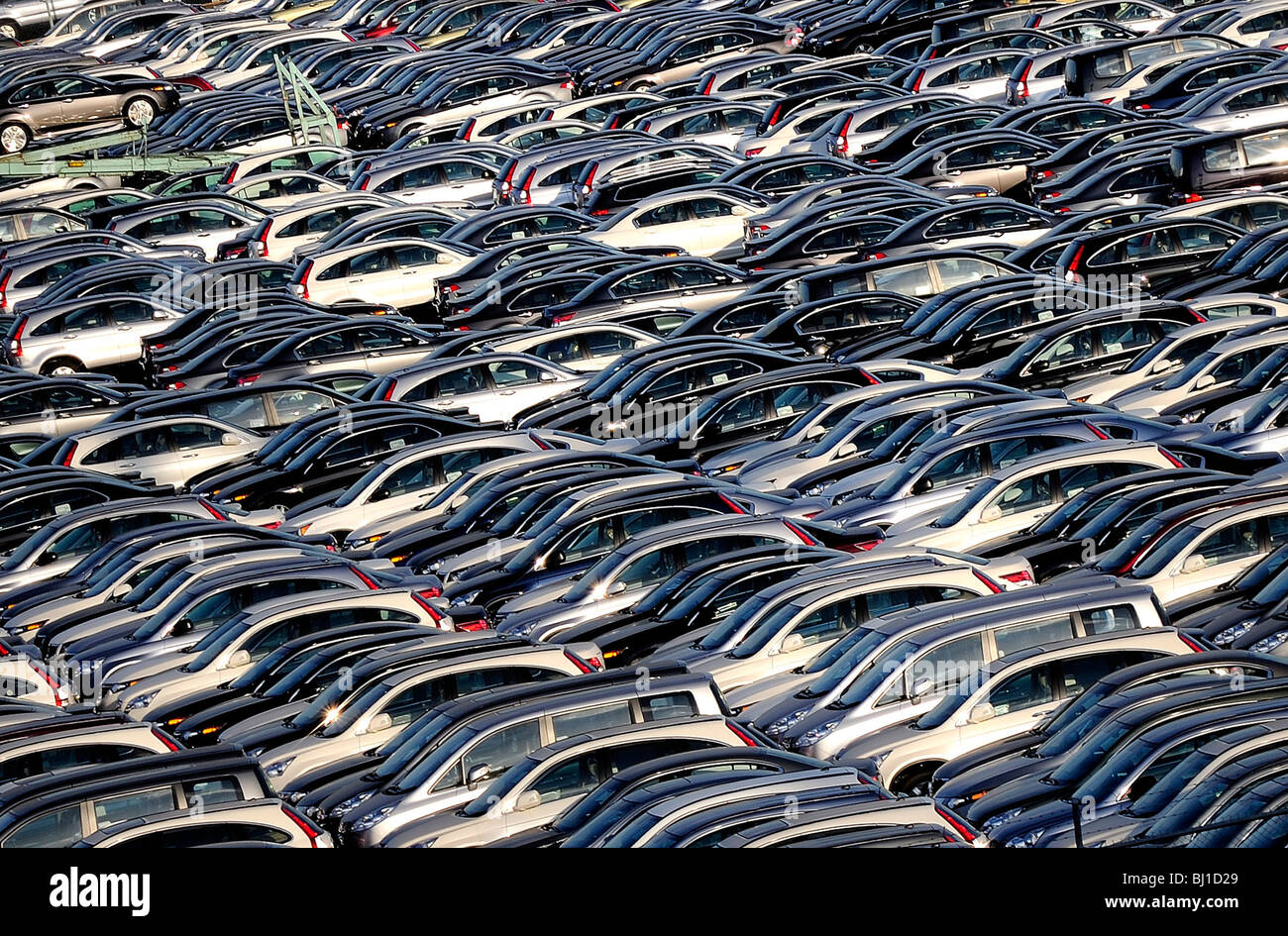 Vehicles await loading onto ships for export at a port in Yokohama, Japan. - Stock Image