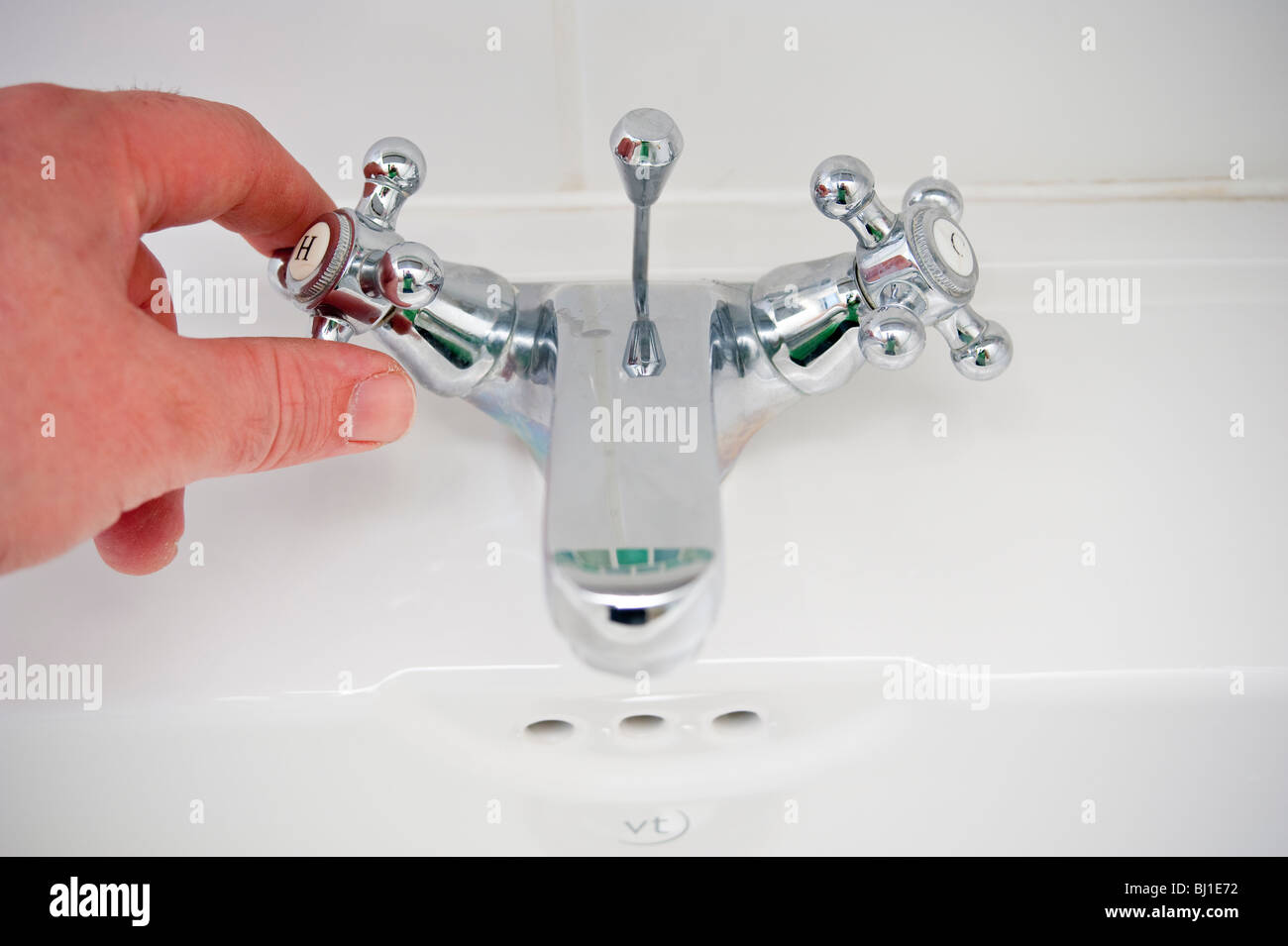 A MODEL RELEASED picture of someone turning the hot tap on in the uk - Stock Image