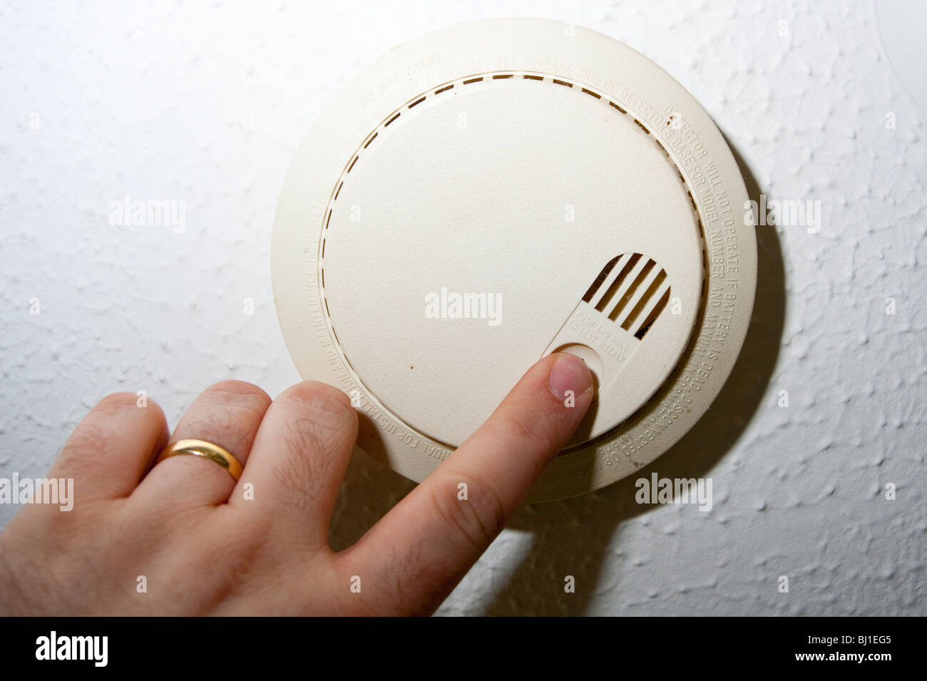 A MODEL RELEASED picture of someone testing the smoke alarm in the uk - Stock Image