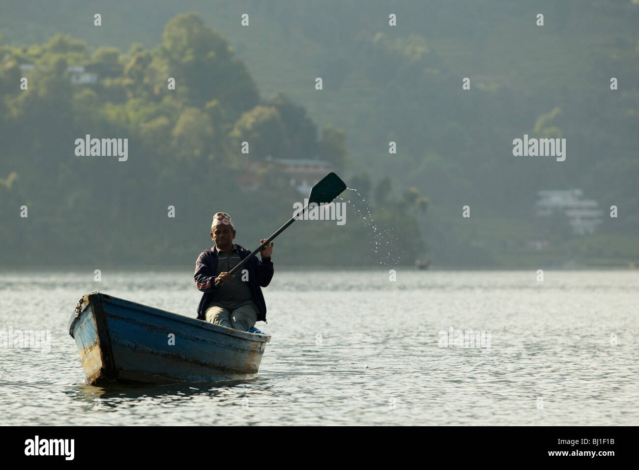 A man rowing in a canoe on Pewha Lake in Pokhara, Nepal on Monday October 26, 2009. - Stock Image