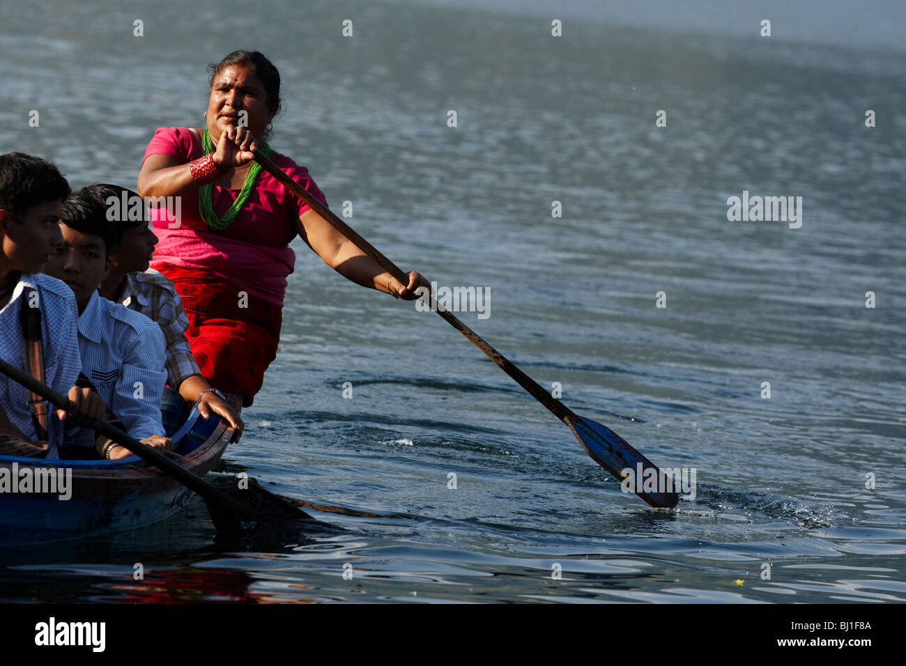 A woman steers a canoe on Pewha Lake in Pokhara, Nepal on Monday October 26, 2009. - Stock Image