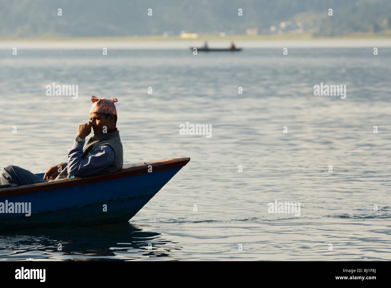Man sitting in a canoe on Pewha Lake in Pokhara, Nepal on Monday October 26, 2009. - Stock Image