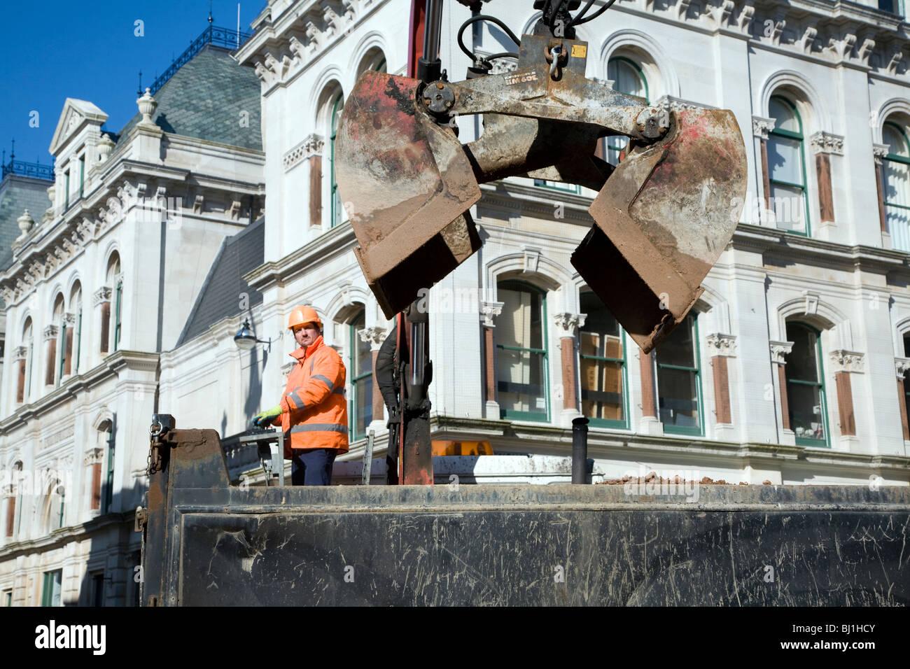 Man operating hydraulic grab machine on lorry - Stock Image