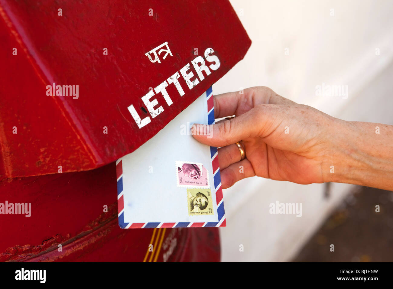India, Kerala, Kochi, Fort Cochin, woman's hand posting air mail letter in post box - Stock Image