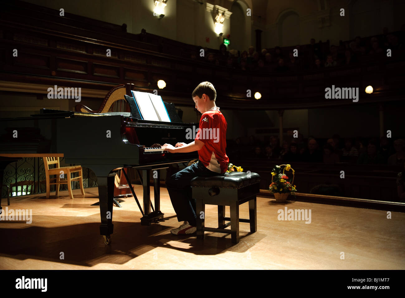 A young teenage boy competing in a music competition playing the grand piano in a small concert hall, UK - Stock Image