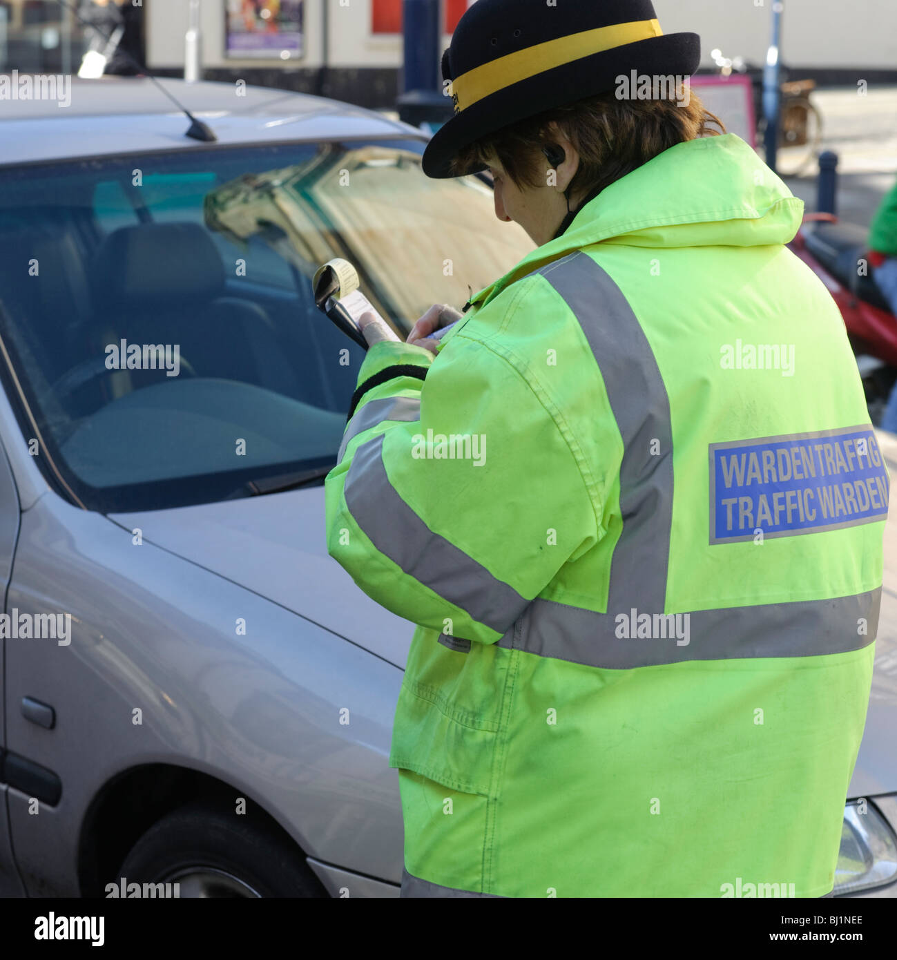 A female traffic warden writing or issuing a parking ticket, Aberystwyth Wales UK - Stock Image