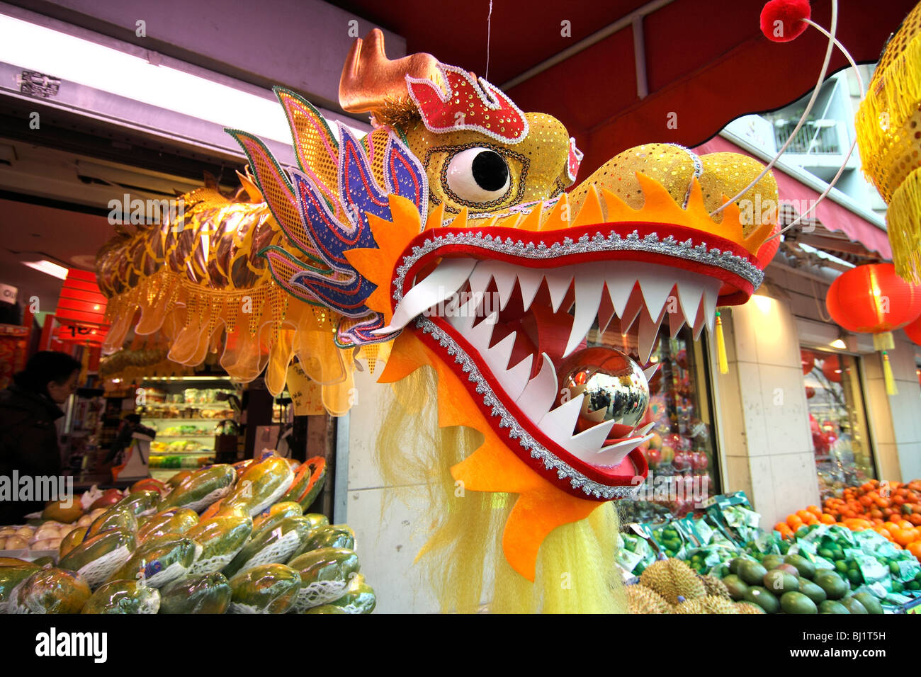 a dragon head jumping out of a shop at the chinese new year parade