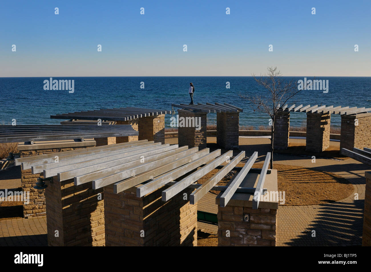 Parkour traceur standing on top of stonehenge structure at Ajax waterfront at the old water plant site at Lake Ontario - Stock Image