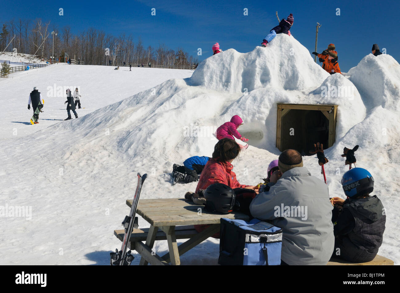 family picnic in the winter snow with children on a snow pile at