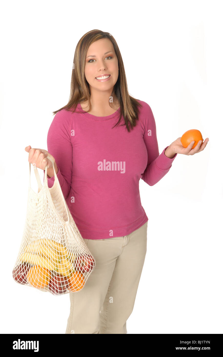 Attractive young woman with reusable grocery shopping bag filled with fresh fruit. - Stock Image