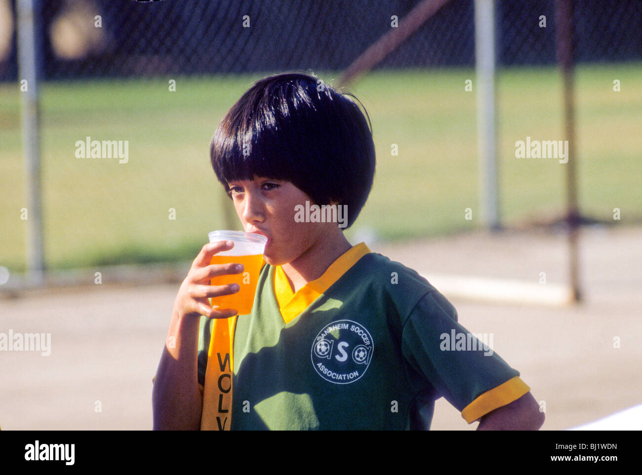 Asian-American boy drinks juice at half-time break during soccer football game in Anaheim, California, USA - Stock Image