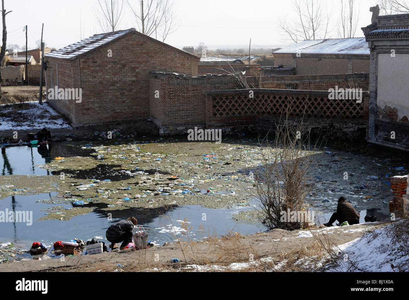 Women washing clothes in a polluted pond in a village in Hebei province, China. 02-Mar-2010 - Stock Image