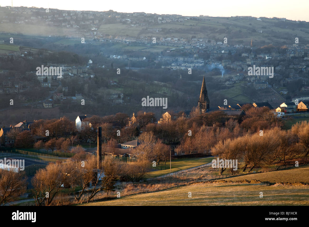 Yorkshire Pennine village nestling in the Colne valley on a bright cold still winter's evening - Stock Image