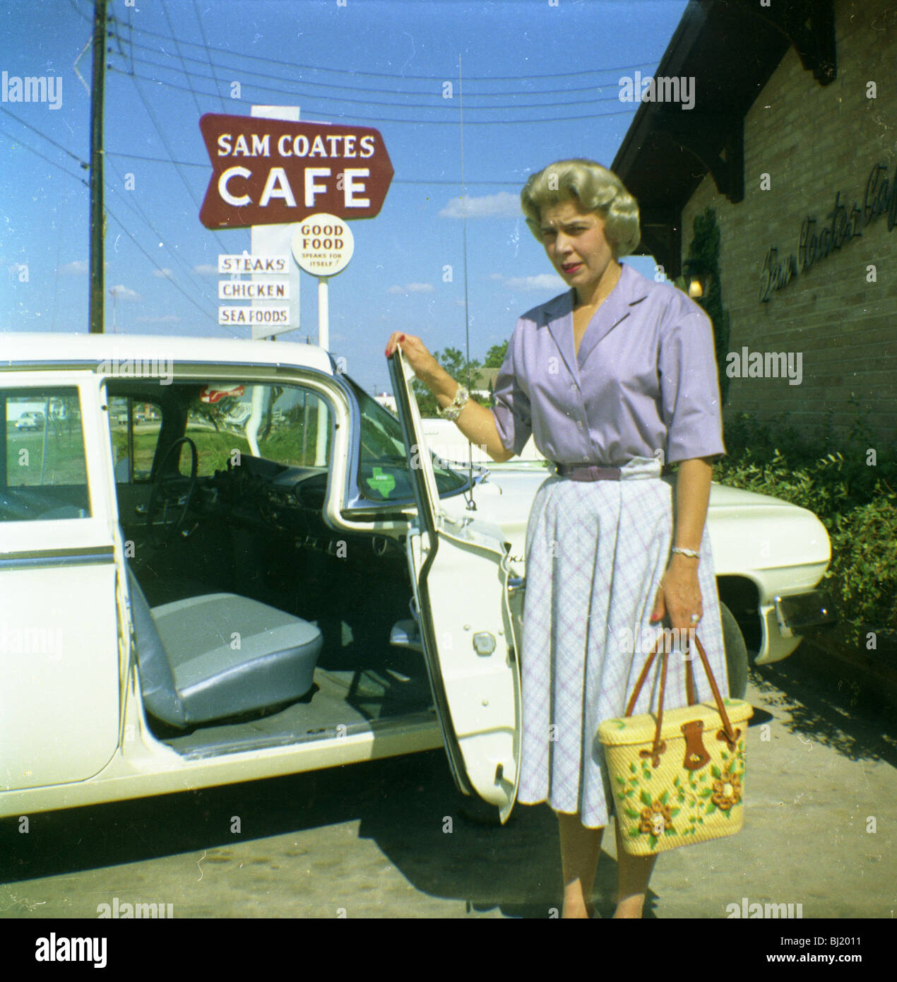 A woman opens the door of her car outside the Sam Coates Cafe in Waco, Texas in the early 1960s. - Stock Image