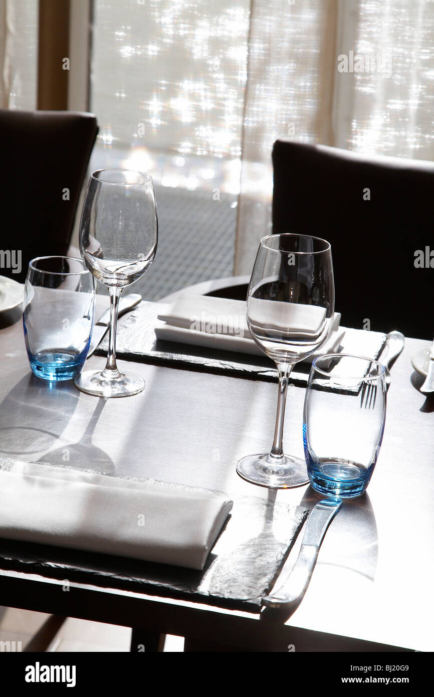 Table setting with water reflections in the background. - Stock Image