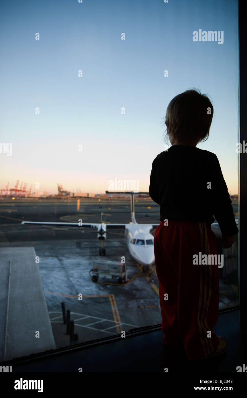 A boy watching a airfield through a window - Stock Image