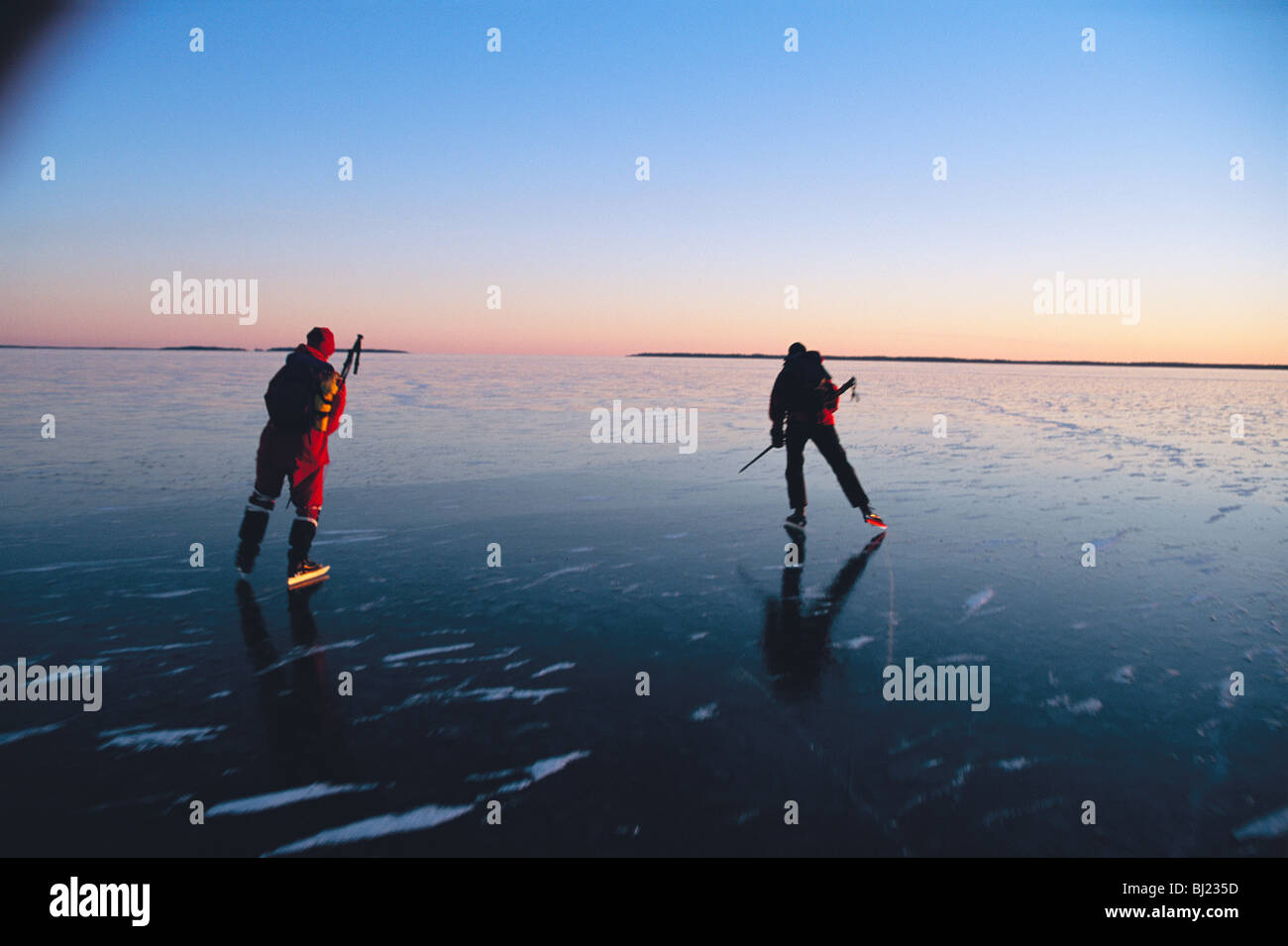 Two people skating on a lake at sunset, Sweden. - Stock Image