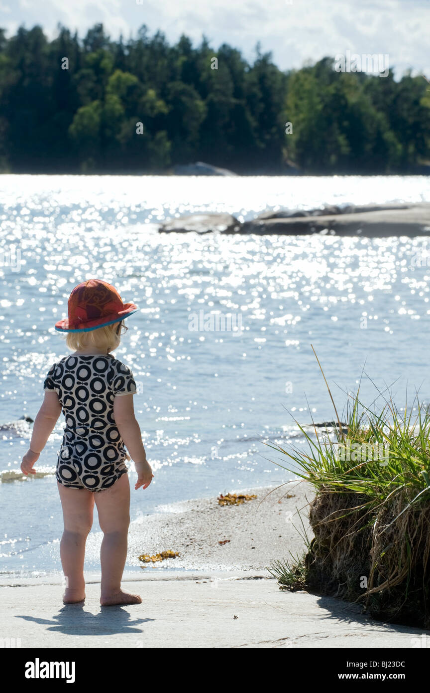 Girl standing by play of sunlight on the surface of water, Sweden. - Stock Image