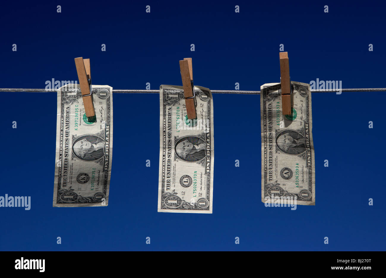 three one dollar bill banknotes hanging on a washing line with blue sky Stock Photo