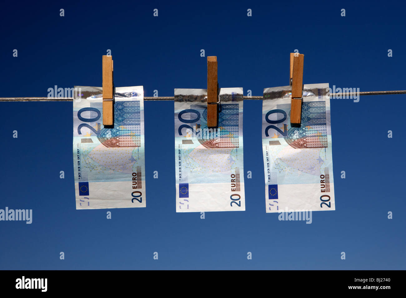 three twenty euro banknotes hanging on a washing line with blue sky Stock Photo