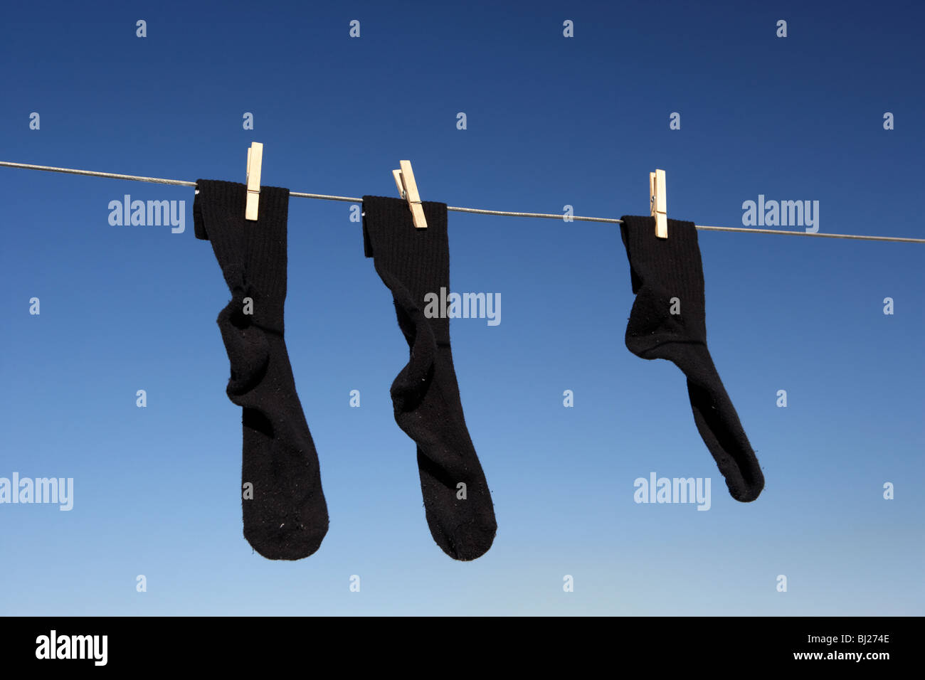 pair of black socks and an odd one hanging on a washing line with blue sky - Stock Image