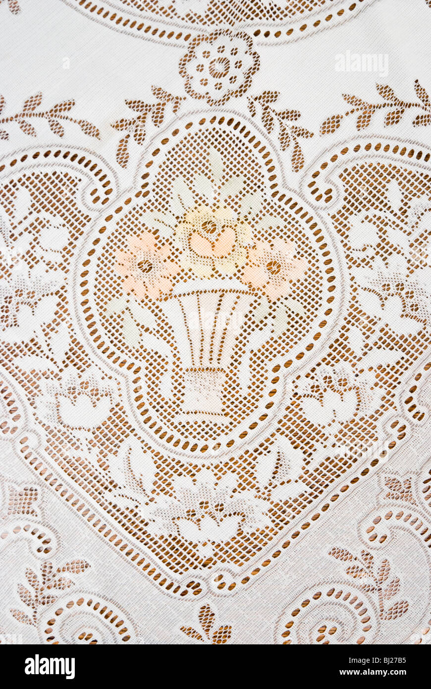 Picture of a lace tablecloth with floral design and vase. - Stock Image
