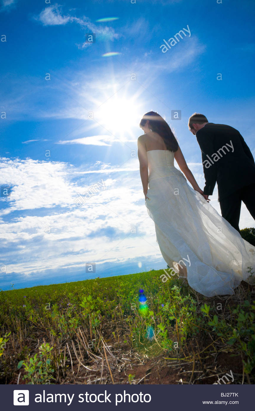 Bride and groom walking on a grass field - Stock Image