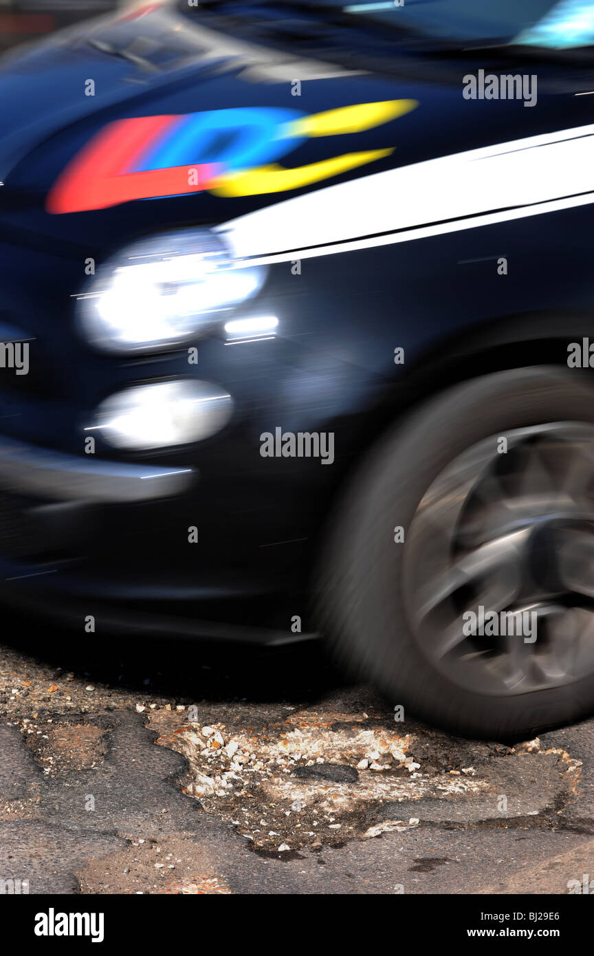 A car drives over a deep pothole in the road - Stock Image