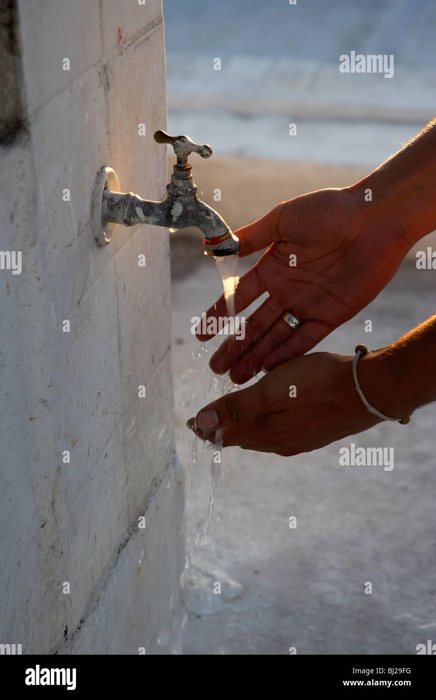 hispanic man washing hands at outdoor tap - Stock Image