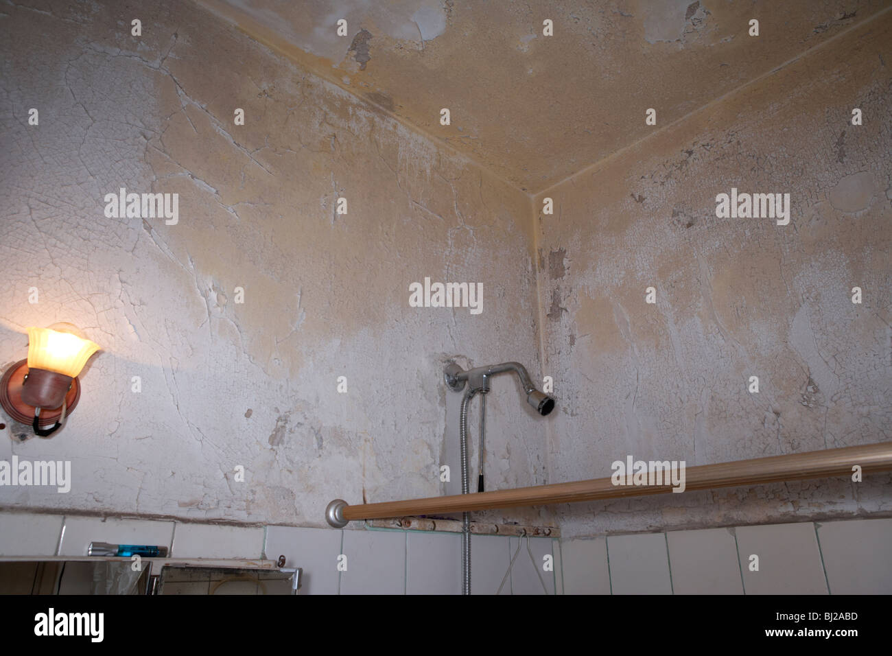 peeling paint on the ceiling above the shower in a run down bathroom Stock Photo